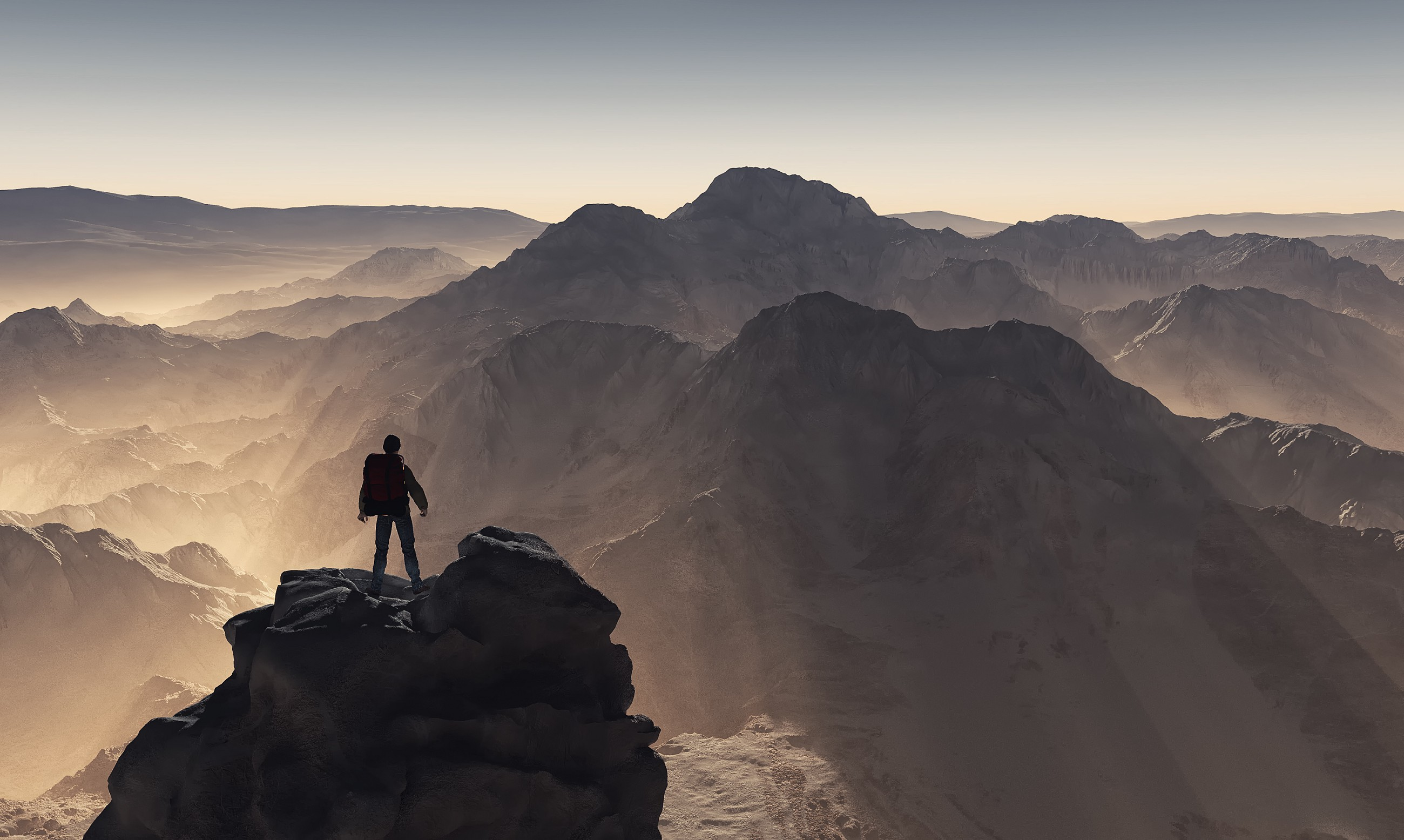 Man standing at the peak of the tallest mountain looking down at other mountains.